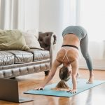 A female yoga instructor demonstrating Downward-Facing Dog to her online yoga class, utilizing her various muscle groups while holding the proper pose..