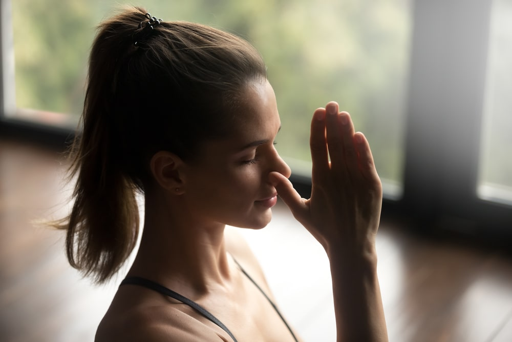 A woman with a pony tail doing alternate nostril breathing exercise.