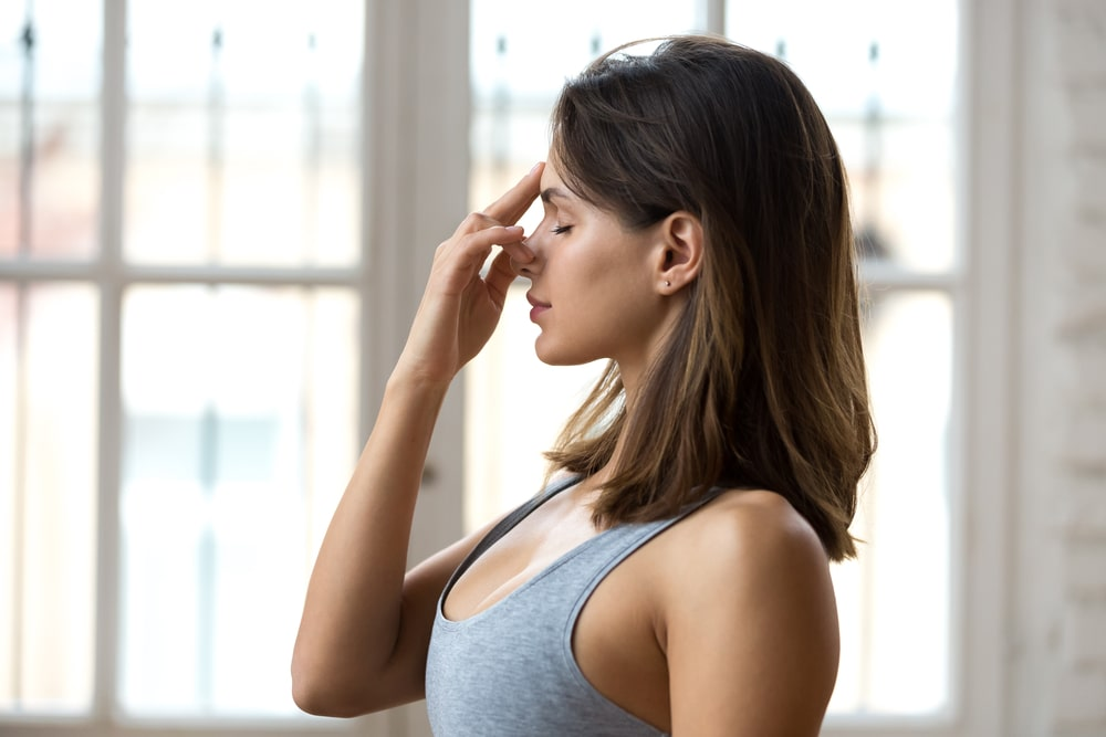 A woman in a gray top doing alternate nostril breathing exercise beside a window.