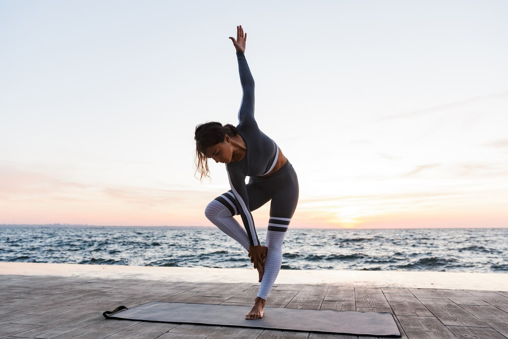 A woman practicing her yoga routine by the beach, wearing matching high-quality yoga pants and top in a gray and white color scheme.