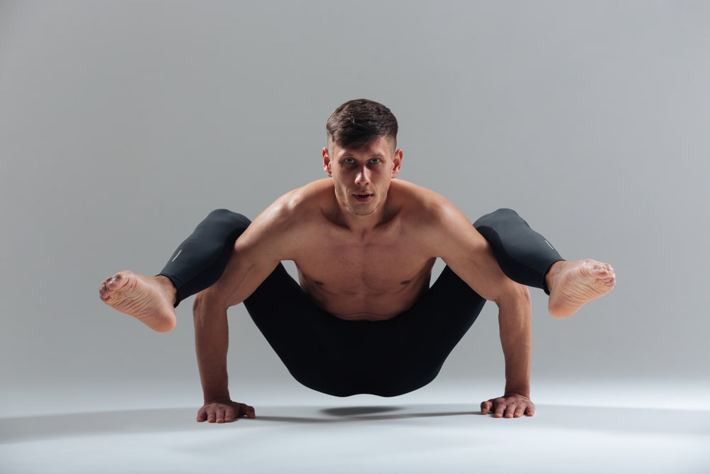 A man wearing a pair of high-quality black yoga pants doing a challenging balance pose for his yoga routine.