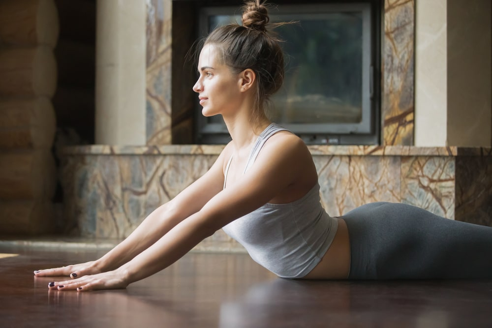A woman in a light gray tank top and dark gray yoga pants, doing Bhujangasana or Cobra Pose on a wooden surface for her yoga routine.