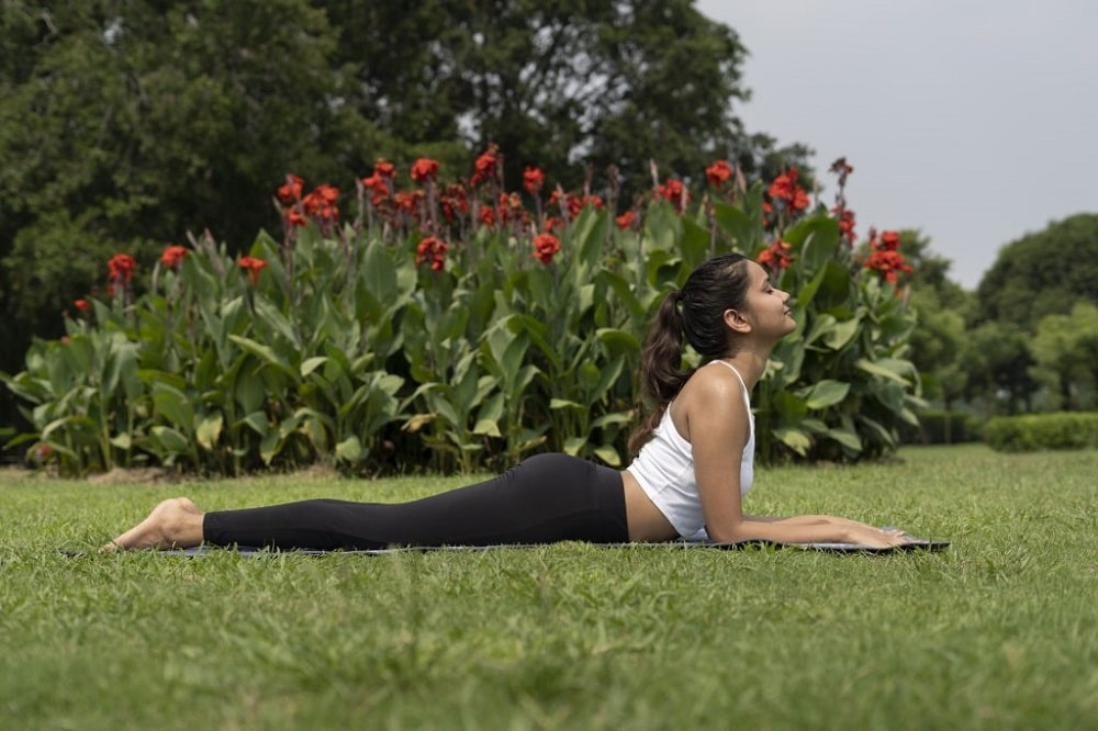 A woman in a white tank top and black yoga pants, doing Salamba Bhujangasana or Sphinx Pose on a grassy lawn for her outdoor yoga routine.