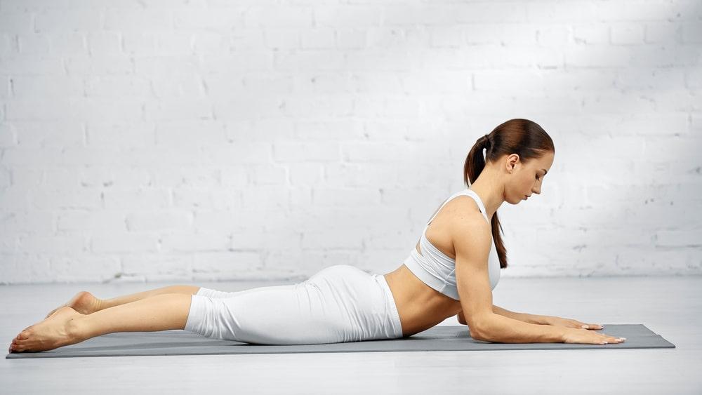 A woman in white yoga activewear, doing Salamba Bhujangasana or Sphinx Pose on a gray yoga mat indoors.