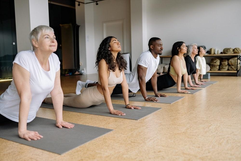 Yoga students simultaneously doing Bhujangasana or Cobra Pose on their gray yoga mats at an indoor yoga studio.