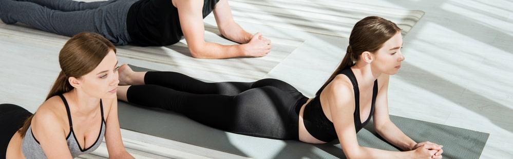 Yoga students simultaneously doing Salamba Bhujangasana or Sphinx Pose on their gray yoga mats at an indoor yoga studio.