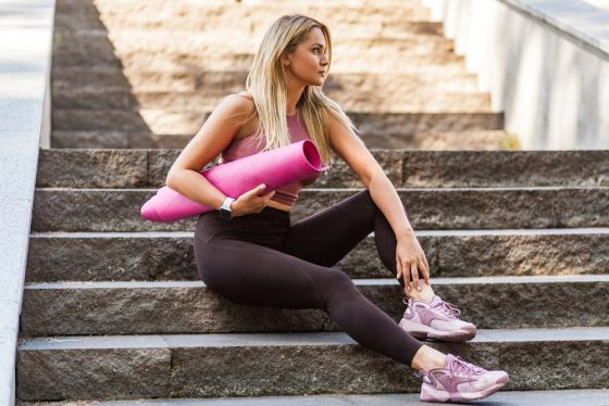 A woman sitting on the steps before the start of her yoga class, carrying a pink yoga mat in her arm and wearing high-quality yoga pants.