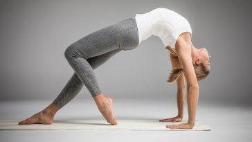 A woman wearing gray yoga pants and a white tank top, practicing Ashtanga or Mysore Yoga on a light-colored yoga mat.