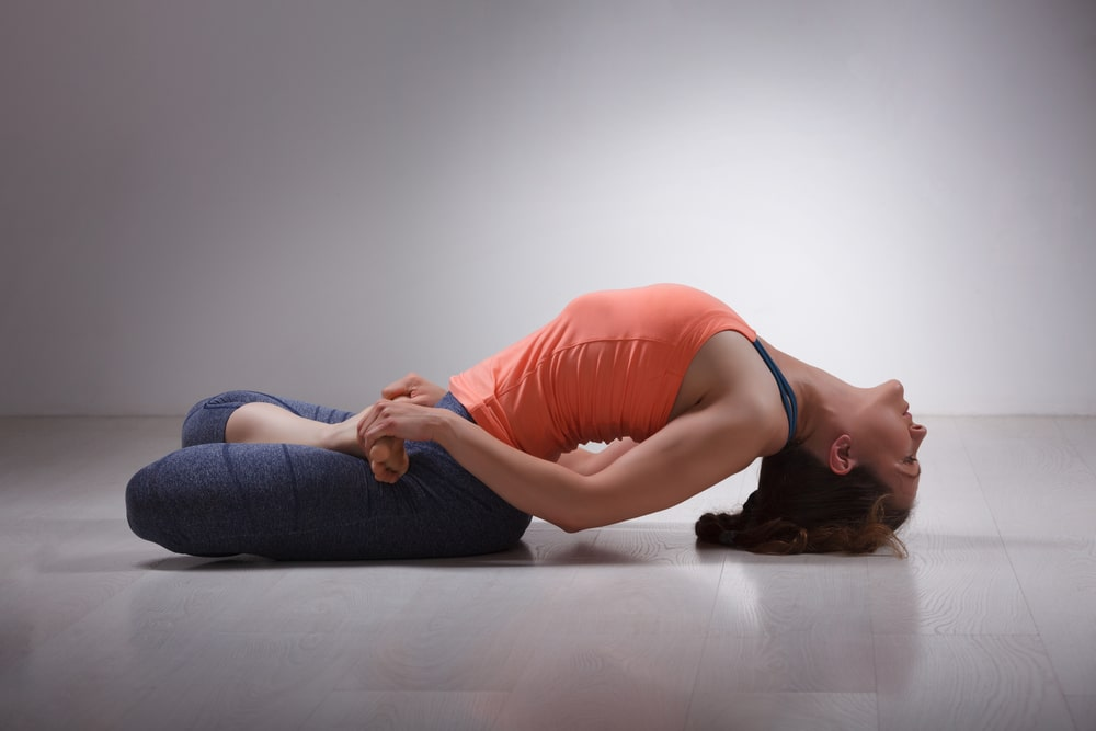 A woman wearing a pair of blue yoga pants and an orange tank top, doing Fish Pose while practicing her Mysore yoga routine.