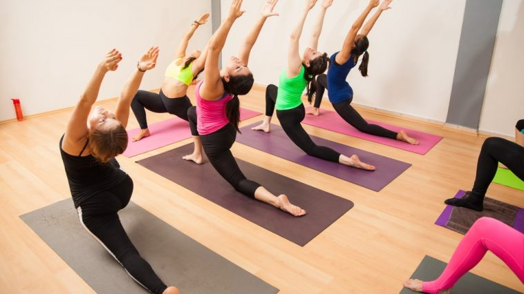 Students practicing Warrior I Pose led by the instructor during a paid yoga class at an indoor studio.
