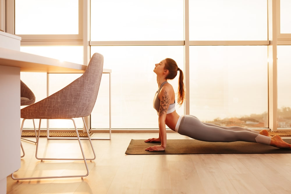 A woman doing her yoga routine at home beside a large window by the dining area.