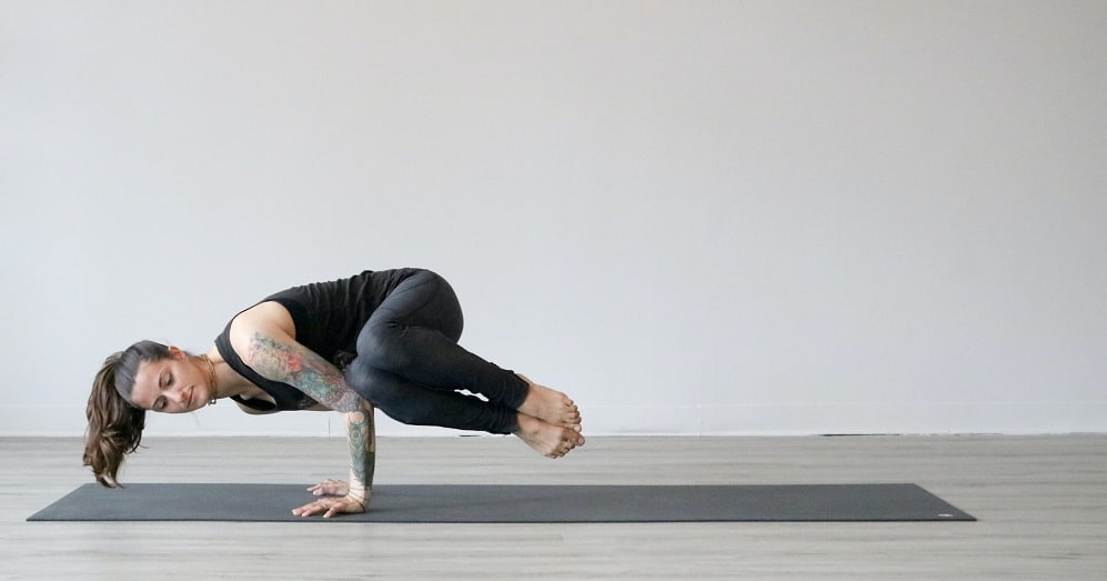 A woman doing her yoga routine, while practicing an advanced yoga pose on a dark gray yoga mat indoors.