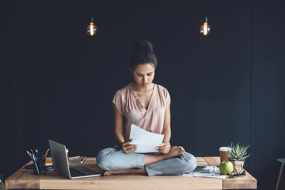 A woman doing her paperwork at her home office while sitting in Lotus position on her desk.