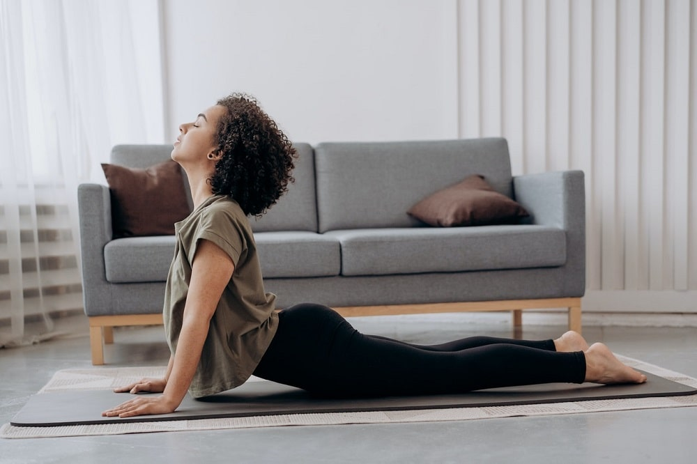 A woman feeling relaxed while holding her Upward Facing Dog Pose on a light gray yoga mat inside her living room.