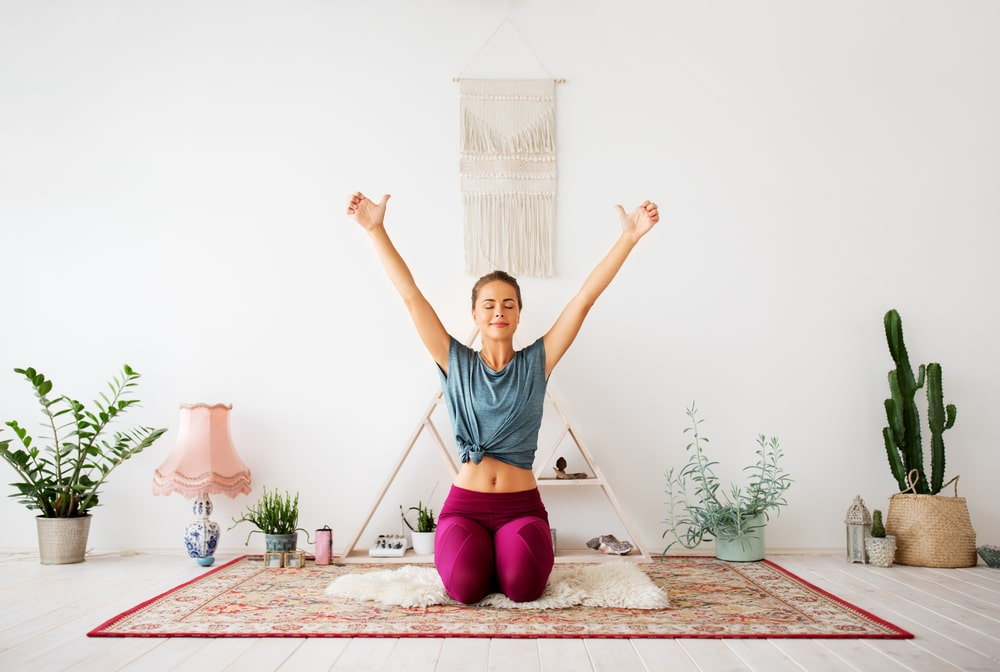A woman with her arms raised and feeling relaxed while practicing her yoga routine at home.