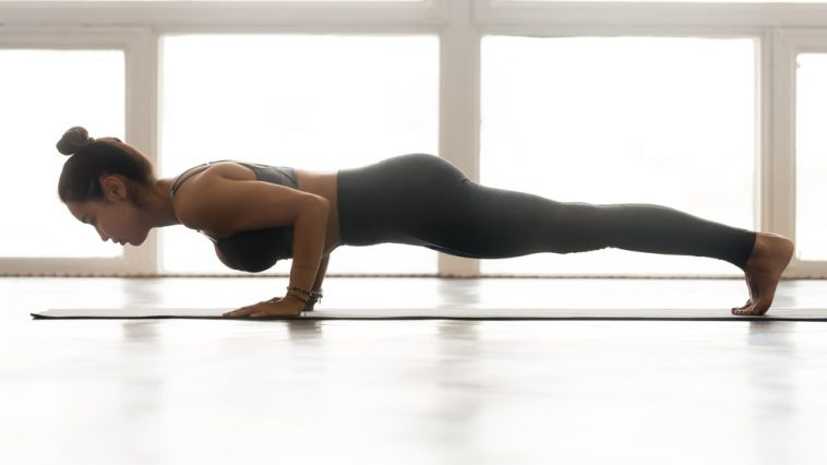 A woman doing a push-up on a yoga mat beside a large window.