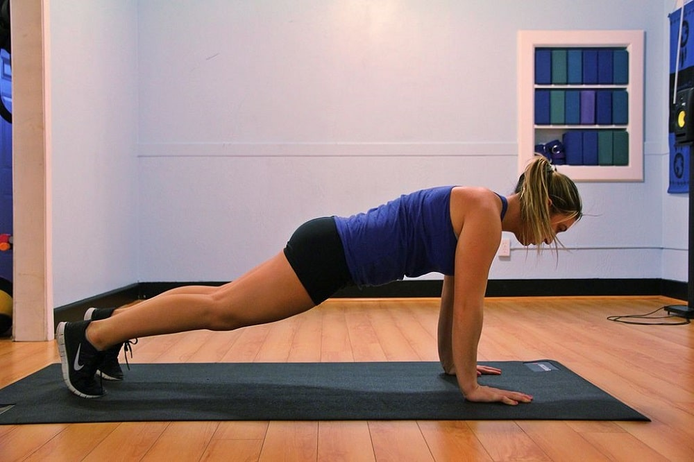 A woman doing Plank Pose on a blue yoga mat inside an exercise studio with wooden floors.