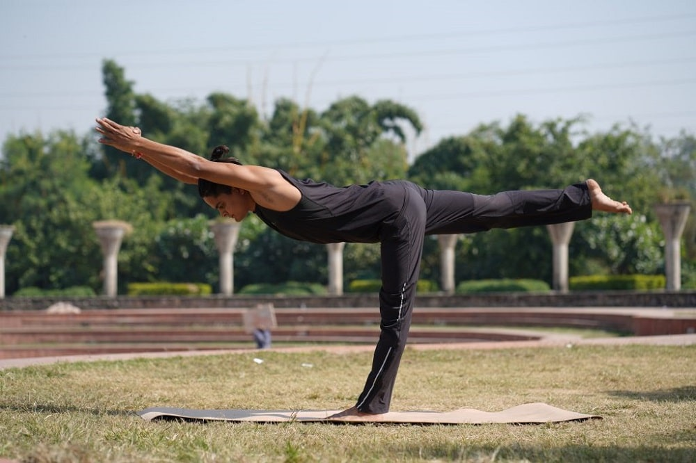 A guy doing Warrior 3 pose while moving with his breath during an outdoor yoga session.