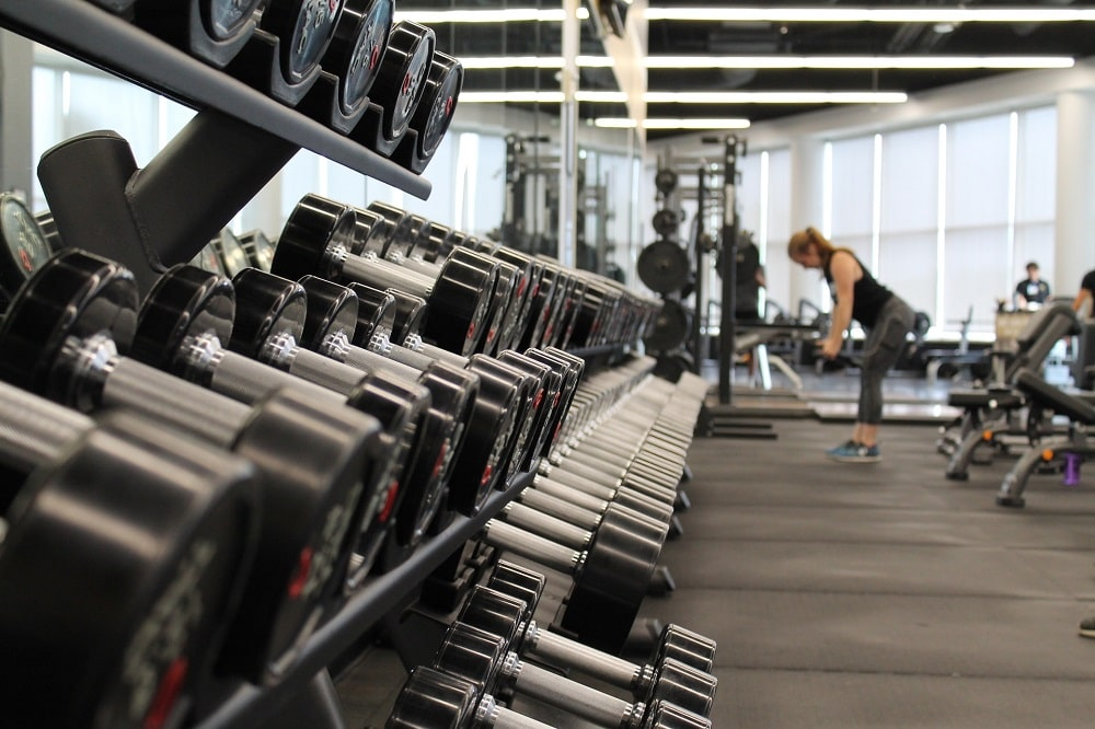 Dumbbells of various weights arranged in a gym, with a woman lifting weights and working out in the far back.