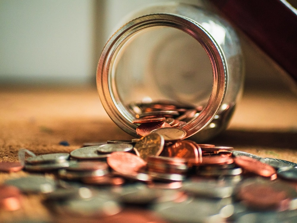 A near-empty jar on its side with coins spilled out and scattered all over the surface.