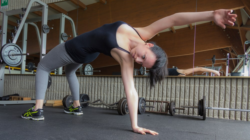 A woman doing yoga and preparing to do Side Plank Pose at an indoor gym with free weights and other exercise equipment around her.