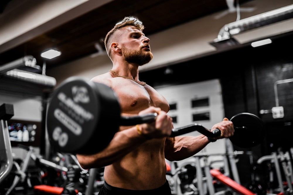 A muscular guy focusing on his heavy weightlifting inside the gym with various equipment surrounding him.
