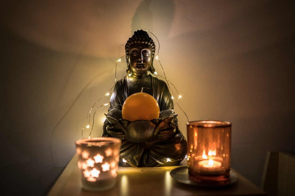 A Buddha with string lights and two lit candles for creating a meditative atmosphere.