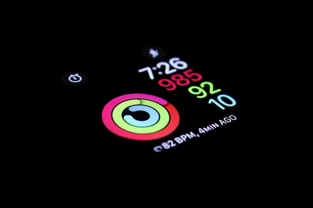 A close-up of a smart watch showing the heart rate, along with the time and other stats on display against a dark background.