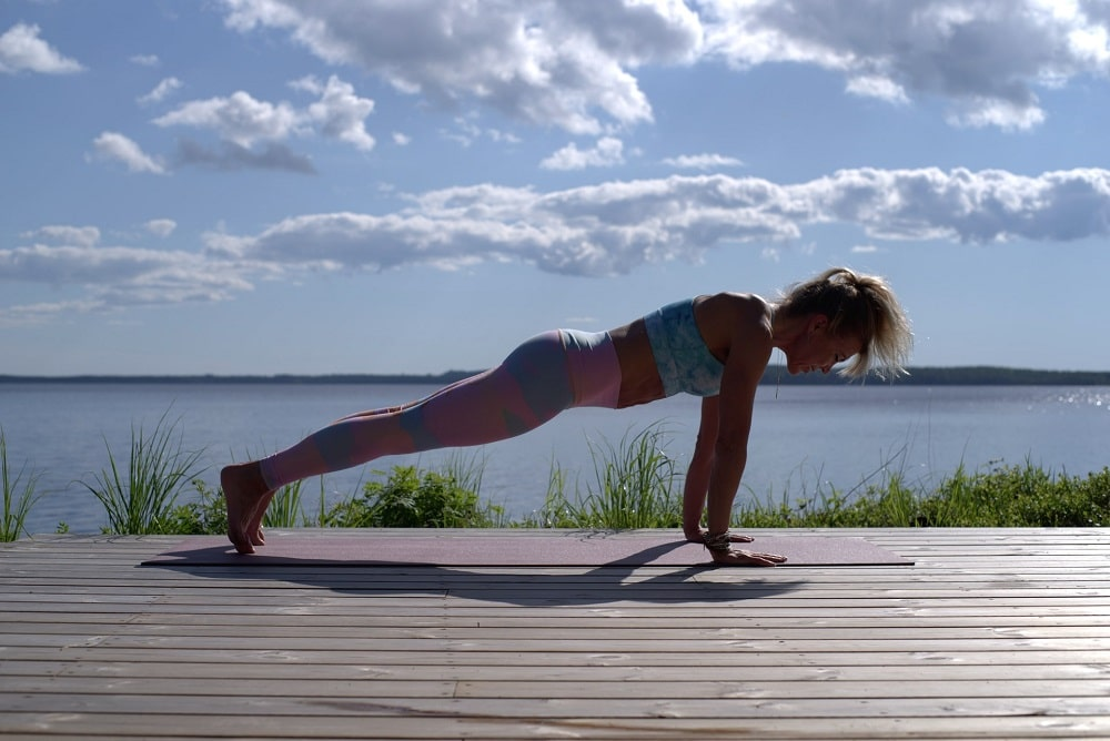 A woman demonstrating her strength while holding a plank position during her yoga routine outdoors.
