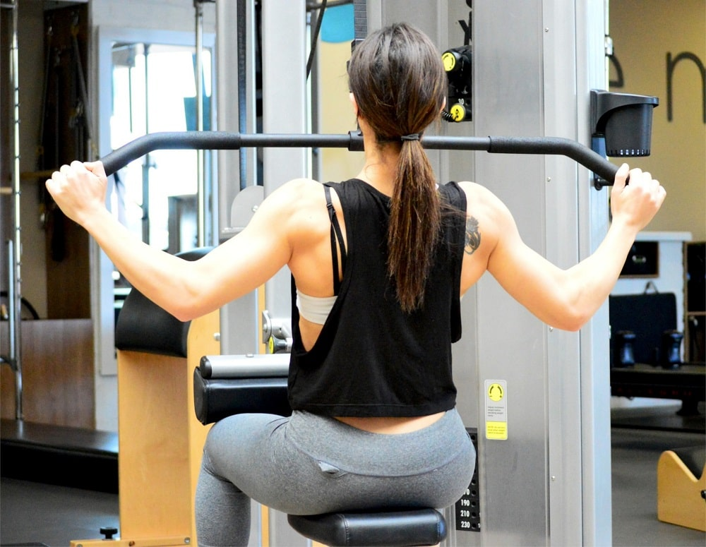 A woman doing her upper body workout at the gym using adjusted weights on an exercise machine.