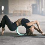 A female yogi doing yoga training with a yoga wheel on a dark gray yoga mat indoors.