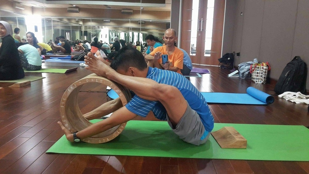 A yoga doing Tortoise Pose assisted by a wooden yoga wheel on a green yoga mat.