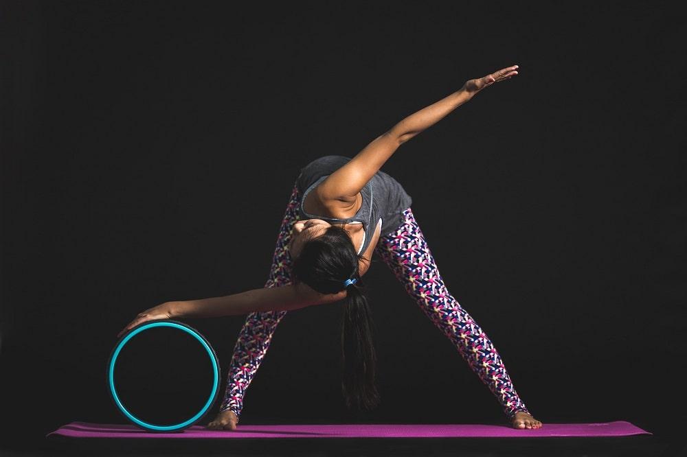 A female yogi doing Wide-Legged Forward Fold with a Twist assisted by a turquoise yoga wheel on a purple yoga mat.