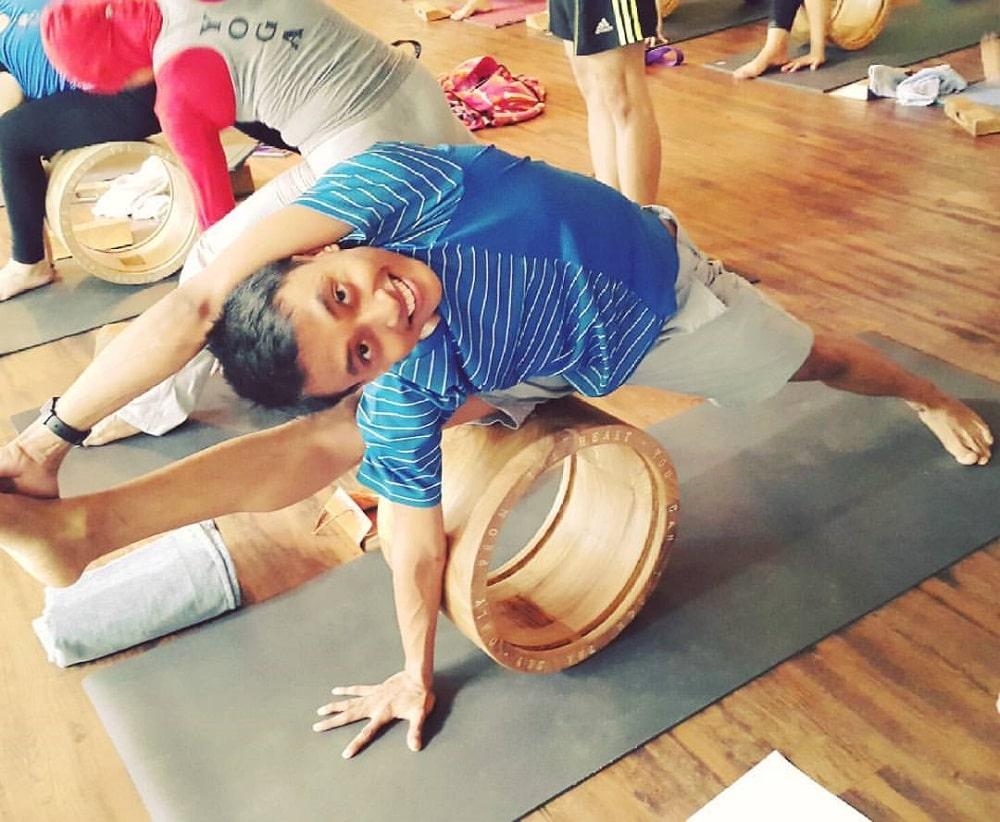 A yogi doing Visvamitrasana assisted by a wooden yoga wheel on a dark gray yoga mat.