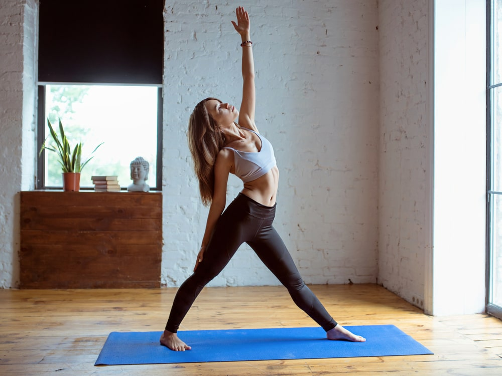 A sporty female wearing a high-quality light gray top and black yoga pants, while doing Peaceful Warrior Pose on a blue yoga mat indoors.