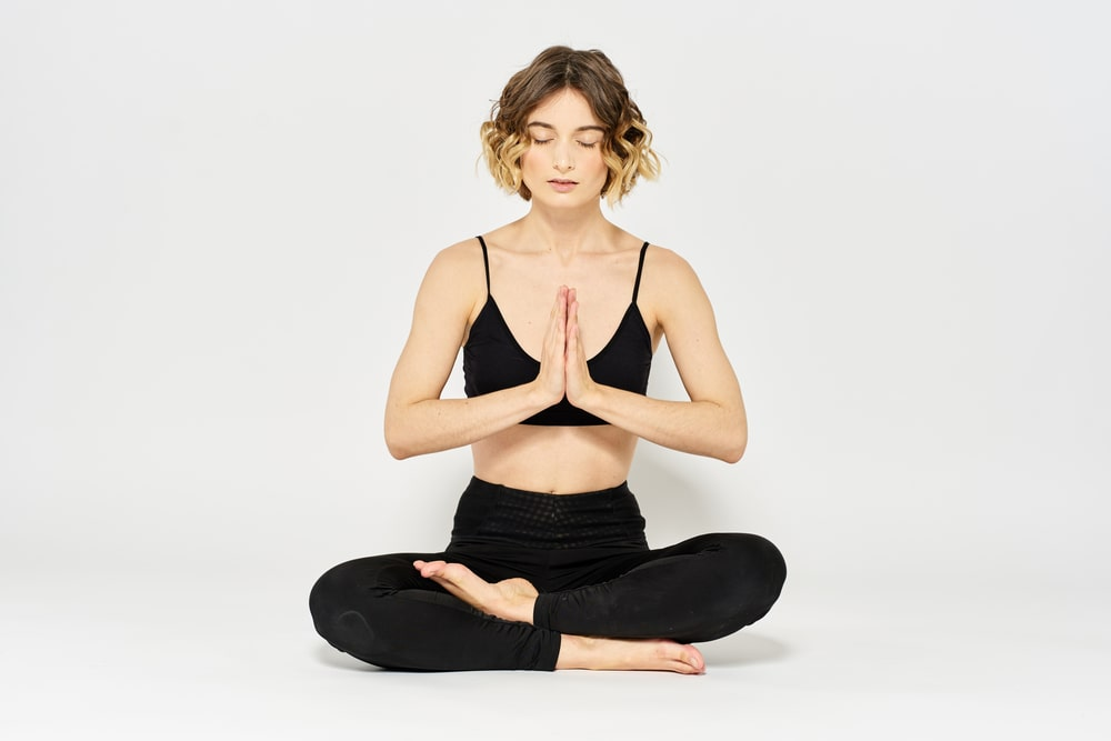 A woman in a black sports top and matching high-rise yoga pants, sitting in Lotus Pose with praying hands, meditating during a yoga session.