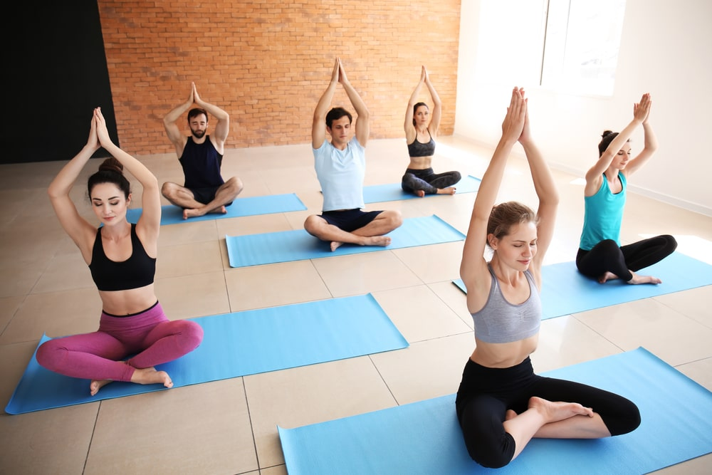 Yoga students in Lotus Pose with arms raised in prayer position, meditating in their various yoga wear on their blue yoga mats.