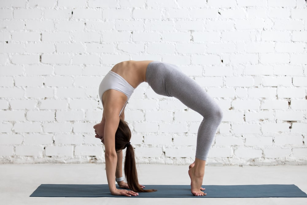 A woman maintaining her balance while doing Bridge Pose on a dark gray yoga mat indoors.