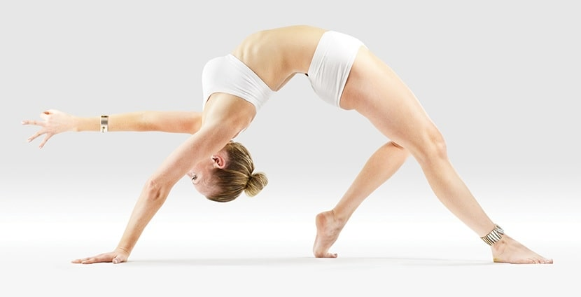 A female yogi doing a backbending pose during a yoga session to strengthen her spine.