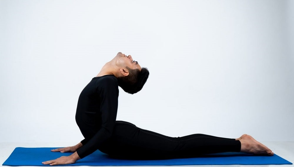 A male yogi doing Bhujangasana or Cobra Pose safely on a blue yoga mat at an indoor studio.
