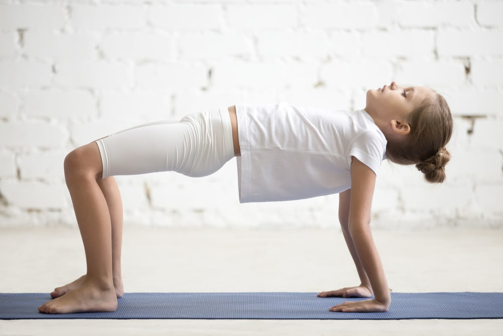 A young girl doing Reverse Tabletop Pose on a gray yoga mat at an indoor studio.
