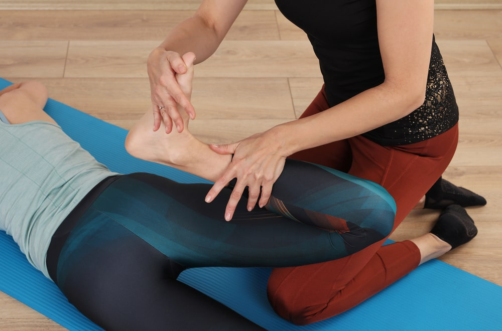A yoga instructor assisting a student with a bad knee through some leg stretching movements after a yoga session.