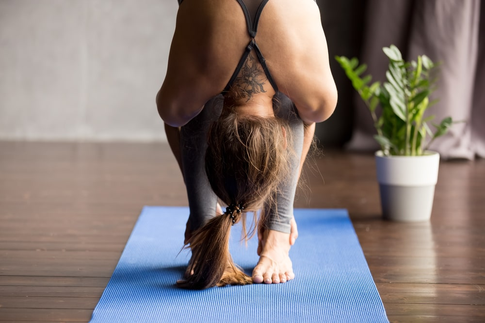 A female yogi doing a head-to-knees exercise as warm-up for her bad knees prior to a yoga session.