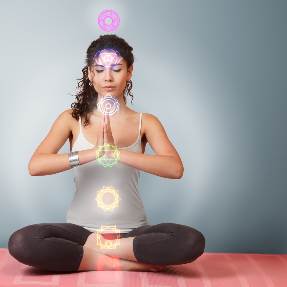 A female yogi meditating on her seven chakras during a yoga session, with illustrations of where each chakra point is located in the body.