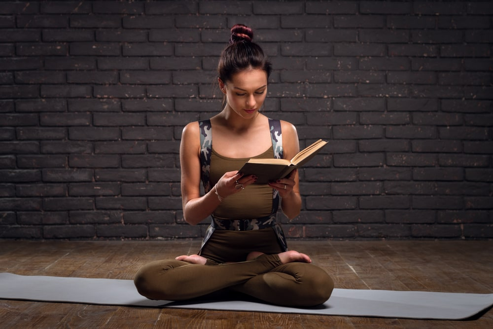 A woman reading a book on yoga and meditation while seated in Lotus Pose on a light-gray yoga mat.