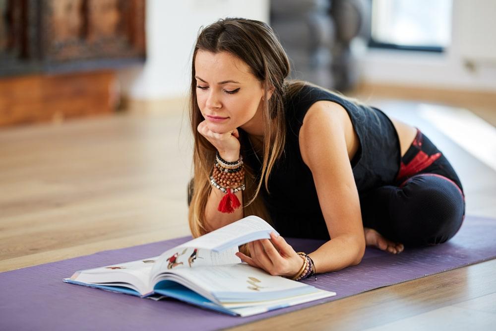 A beginner yogi reading an illustrated hardbound book on yoga and meditation on her purple yoga mat.