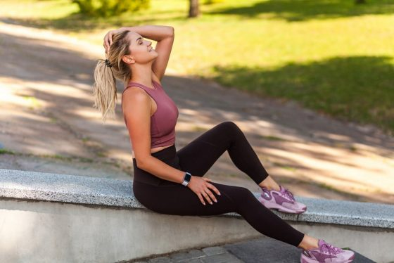 A woman wearing high-quality activewear, resting on a concrete surface and taking a break from her yoga session.