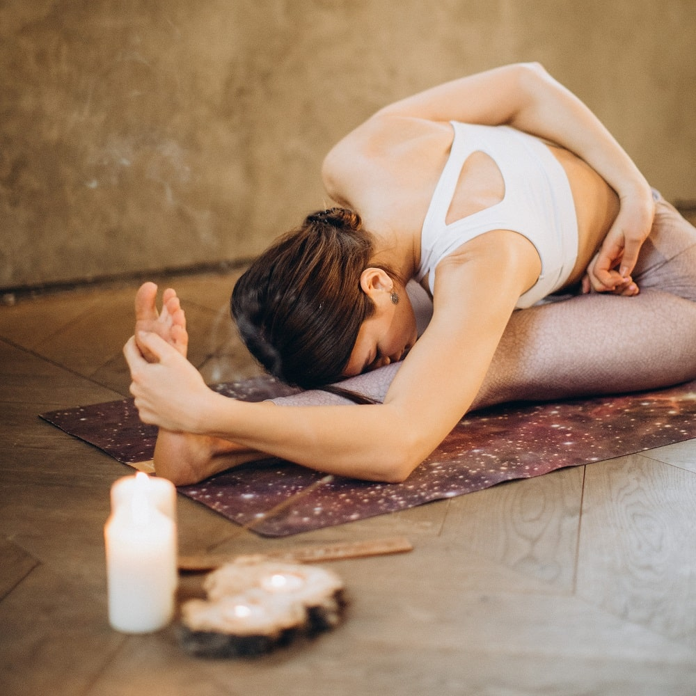 A woman doing Janushirasana or Head-to-Knee Pose while meditating with some incense and candles on the side for her yoga session.