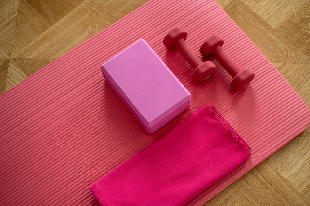 Color-coordinated pink yoga props placed on top of a yoga mat used for modification in Head-to-Knee Pose.