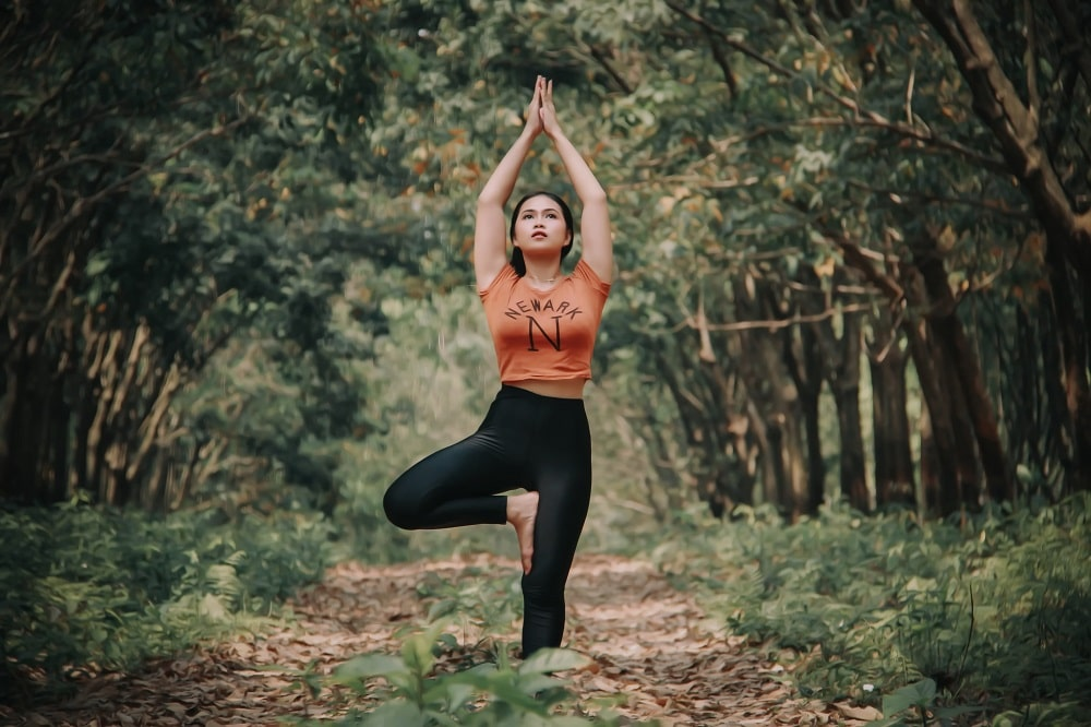 A female yogi doing Tree Pose outdoors, mastering her yoga practice with patience and consistency.
